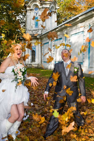 Newly-married couple in autumn park shows activity, a leaf fall from yellow and red leaves Stock Photo - 6106589