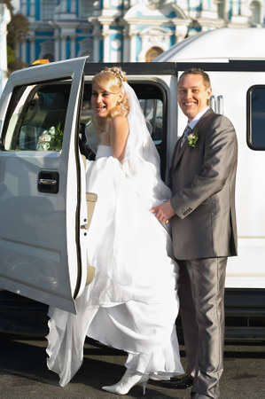 The newly married couple near a white limousine going to drive photo