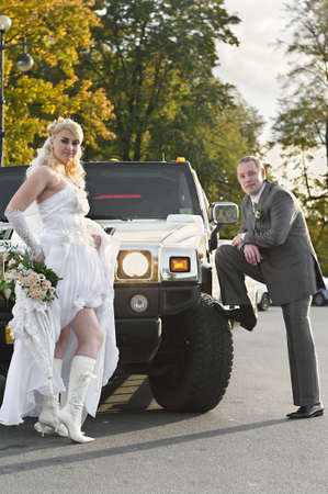 The newly married couple near a white limousine photo