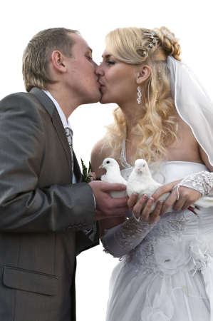 Happy young newlywed couple kissing. Doves in their hands. Isolated over white  photo