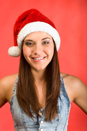 Young beautiful woman in Santa`s hat smiling in camera. Red background Stock Photo - 6135191