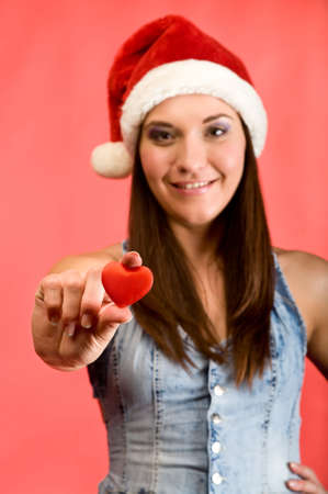Young beautiful woman in Santa`s hat holding red small heart in hands. Red background Stock Photo - 6135199