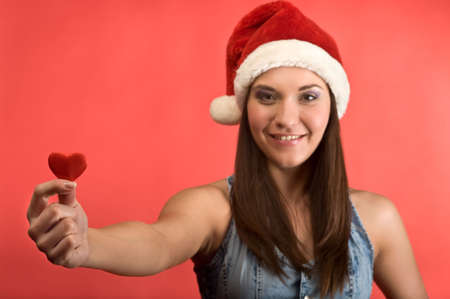 Young beautiful woman in Santa`s hat holding red small heart in hands. Red background. Face not in focus Stock Photo - 6135190