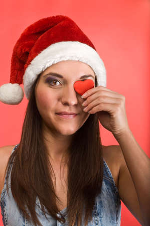 Young beautiful woman in Santa`s hat holding red small heart in hands. Red background Stock Photo - 6135188