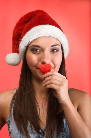 Young beautiful woman in Santa`s hat holding red small heart in hands. Red background Stock Photo - 6135197