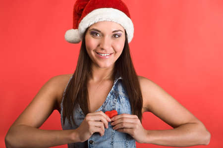 Young beautiful woman in Santa`s hat holding red small heart in hands. Red background Stock Photo - 6135196
