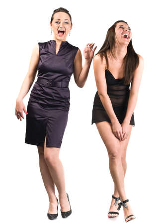 Two young women laugh loudly. Full-length portrait isolated over white background. Cut out photo