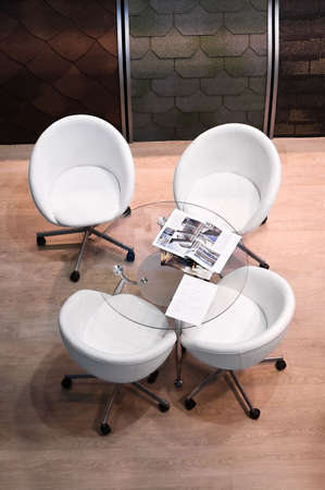 office cabinet: Four white chairs and glass round table in room. Interior of speaking place