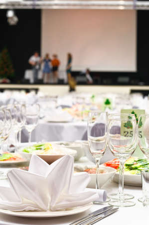 Details of a wedding banquet table setting with background of stage and people the artists. Stock Photo - 6231872