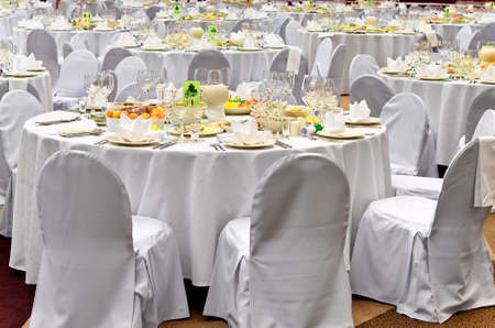 Hochzeit weißen Rezeption Ort für Gäste bereit. Elegante Bankett-Tabellen für eine Konferenz oder einer Partei vorbereitet.