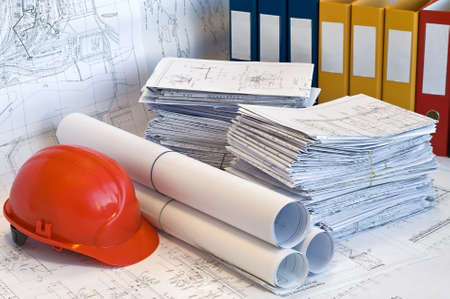 Orange helmet and heaps and rolled project drawings photo