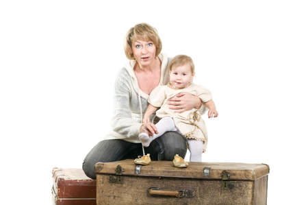 Middle age woman playing with little child a granddaughter. Suitcases oon floor. Isolated on white background photo