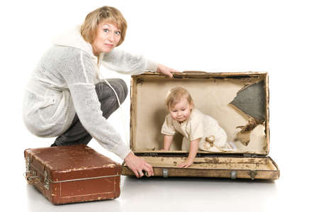 the grand daughter: Middle age woman playing with little child a granddaughter. Suitcases on floor. Isolated on white background. Baby is inside