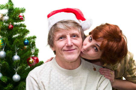 Mature woman kissing a old husband near the Christmas tree. Loving senior couple isolated on white background Stock Photo - 6469042