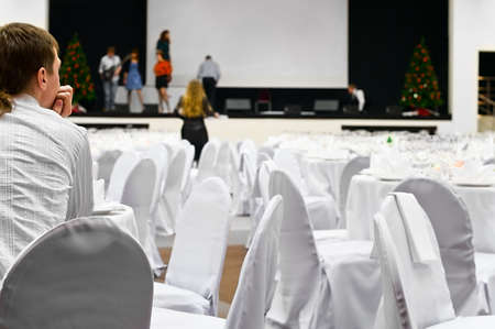 Man sits sit at the table and watchin by the artists on a stage. White wedding tables around. Stage and people on it are not in focus Stock Photo - 6469034