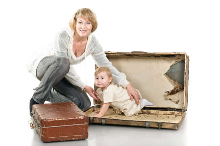 Middle age woman playing with little child a granddaughter. Suitcases on floor. Isolated on white background. Baby is inside photo