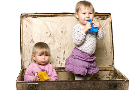 Two little babies playing in sutcase. Sitting iside. Isolated over white background Stock Photo - 6469043