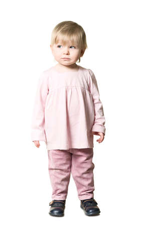One little child standing on floor. Pink clothes. Isolated on white background photo