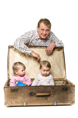 Yappy young father and two little children in ancient big suitcase. Isolated on white background photo