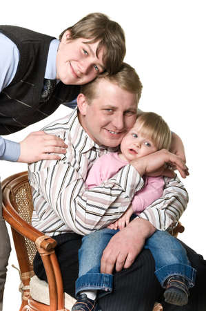 Portrait of happy father with two children: teenage boy and little girl. They are sitting on chair. Isolated on white background photo