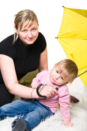 Mother and little child playing on floor with yellow umbrella. Studio shot. Isolated on white background photo