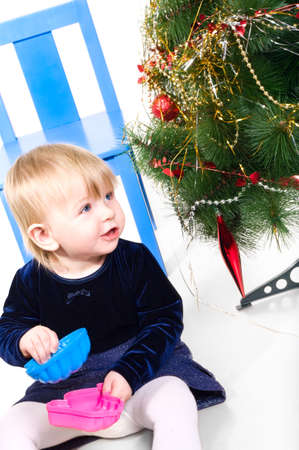 One little child a girl is playing near the Christmas tree on chair. Isolated on white background.  photo