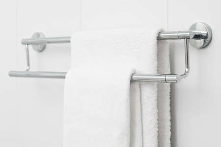 Two white bath towels hanging on white tile wall photo