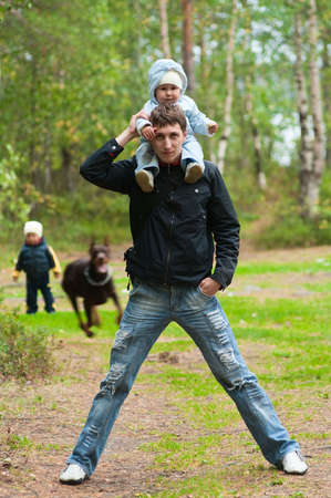 Young father walking with two children and dog. Little girl on shoulders and son and dog on background. Summer time photo