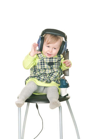 The happy small child sits on a chair in headset ear-phones with a microphone. Isolated on white background photo
