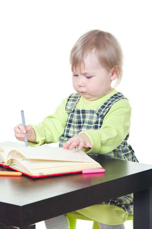 The little girl sits at a table and does a homework, draws in a notebook. It is isolated on a white background photo