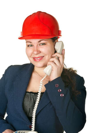Young woman architect in red helmet calling by phone. Isolated on white background photo