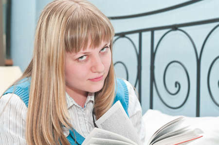The girl the blonde reads the book lying on a bed Stock Photo - 6866063