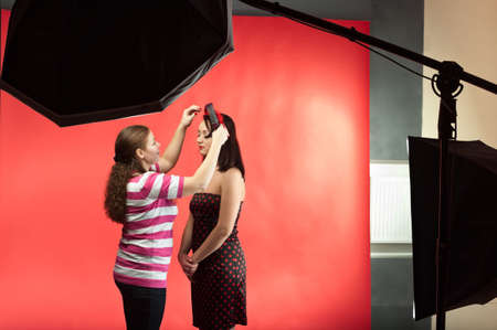 Stylist make image of contemporary model in photographic studio. Two young women. Photo equipment photo