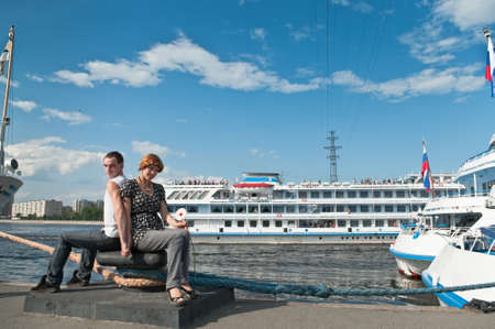 Loving couple teenagers near the cruise liners on harbor photo