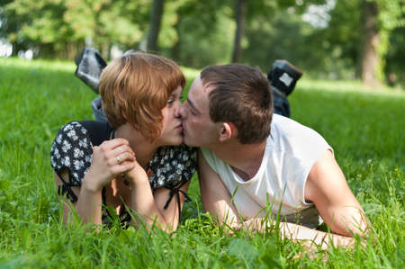 Young loving couple teenagers lying on green grass and kissing photo