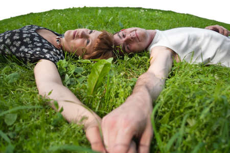 Young loving couple teenagers sitting on green grass. Two Caucasian people photo