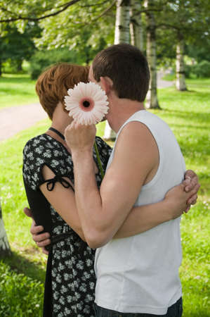 Young loving kissing couple teens. Two Caucasian people. Teenagers: girl and boy embracing one another photo