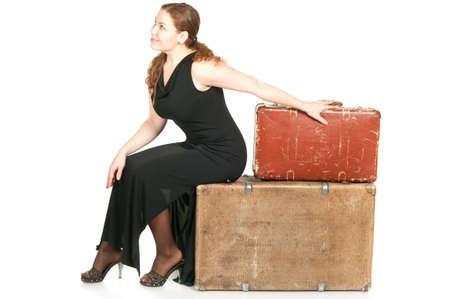 One beautiful woman in black dress dragging two ancient suitcases. Isolated on white background. photo