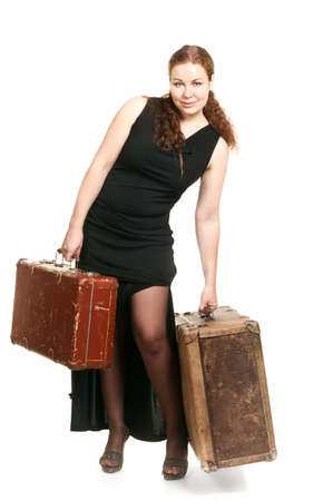 One beautiful woman in black dress and two ancient suitcases the luggage. Isolated on white background. photo