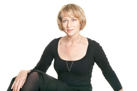 only mature women: Mature woman in black dress sitting. Studio shot on white background