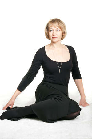 Mature woman in black dress sitting. Studio shot on white background photo