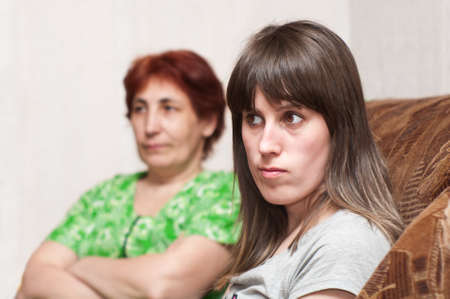 Mature woman a mother and young girl a daughter together on sofa photo