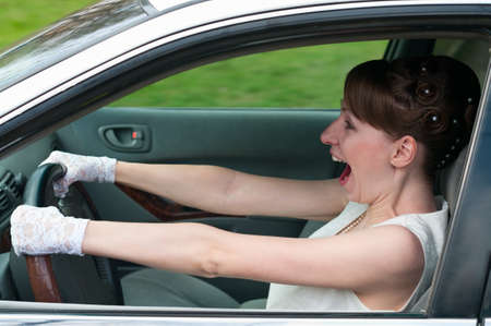 Woman in white dress and white-gloved driving a car and screaming. Looking forvard photo