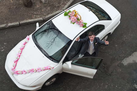 Groom receive bride with open near a white wedding car. Top view photo