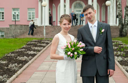 Young loving wedding couple with bunch of flowers. Newlywed pair near registry office photo