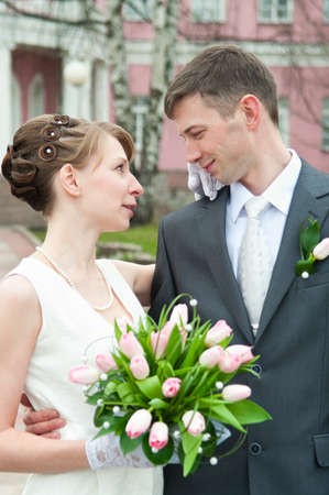 Young loving wedding couple with bunch of flowers. Newlywed pair Stock Photo - 7135167