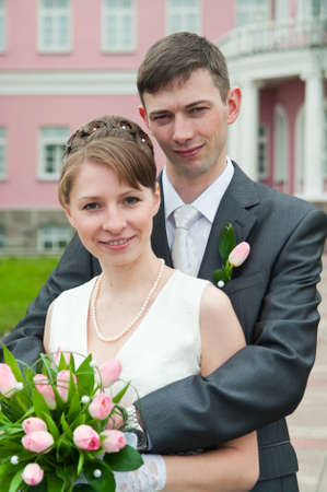 Young loving wedding couple with bunch of flowers. Newlywed pair Stock Photo - 7135214