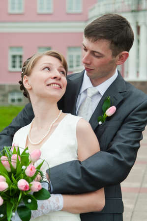Young loving wedding couple with bunch of flowers. Newlywed pair Stock Photo - 7135172