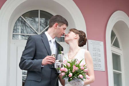 Bride and groom standing near registry office with glasses of champagne and kissing. Caucasians. Young wedding couple Stock Photo - 7135220
