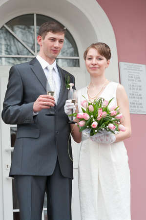 Bride and groom standing near registry office with glasses of champagne. Caucasians. Young wedding couple Stock Photo - 7135242